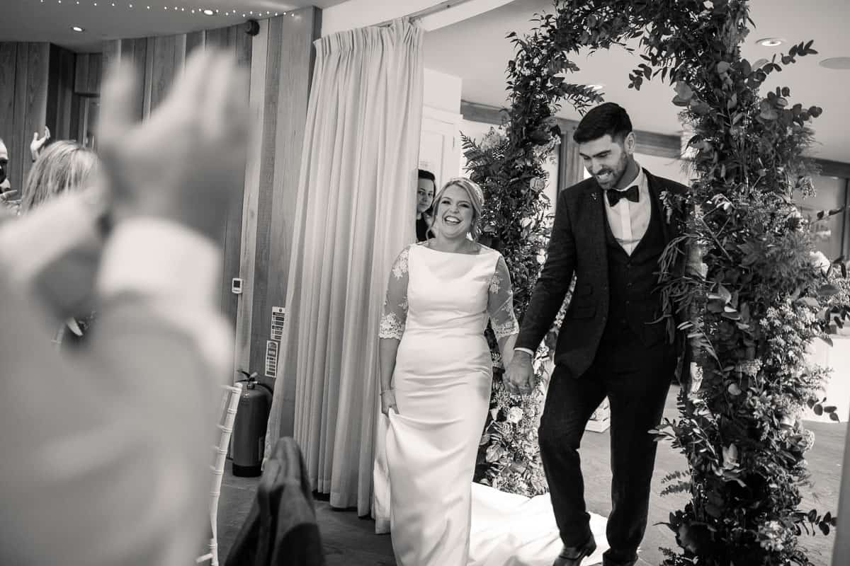 bride and groom walking into the room whilst guests clap and cheer