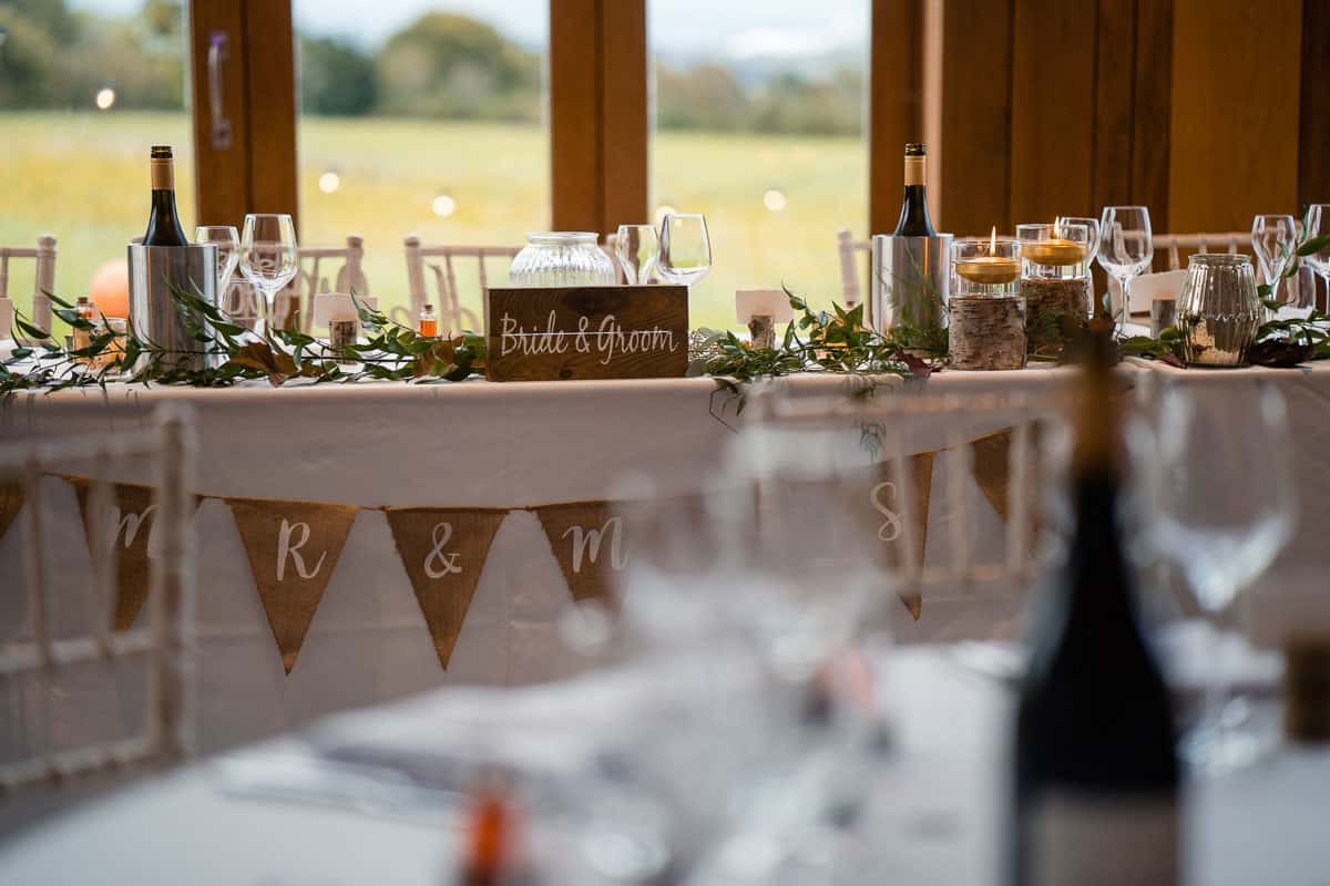 bride and groom wooden sign on the top table