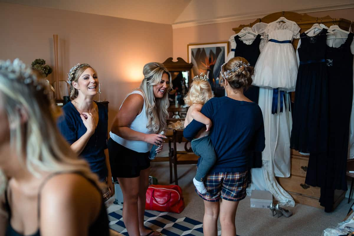 guests laughing as they get ready with the bride in the bridal suite