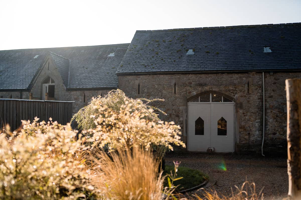 outside view of the Wyresdale Park wedding barns with the sun coming up over the roof and plants in the foreground