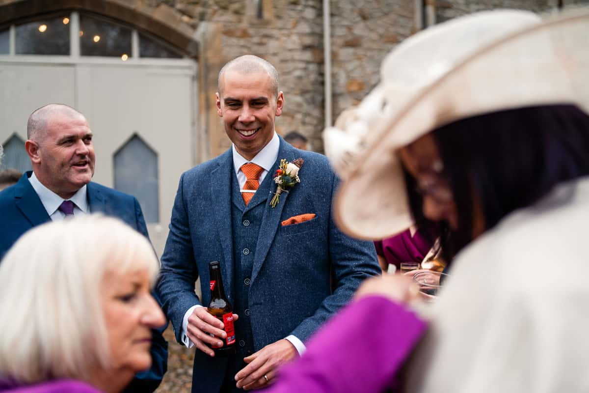 member of the wedding party smiling with a beer in hand