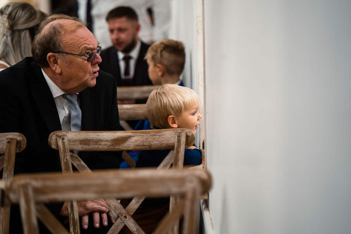 little boy looking through window in the ceremony barn