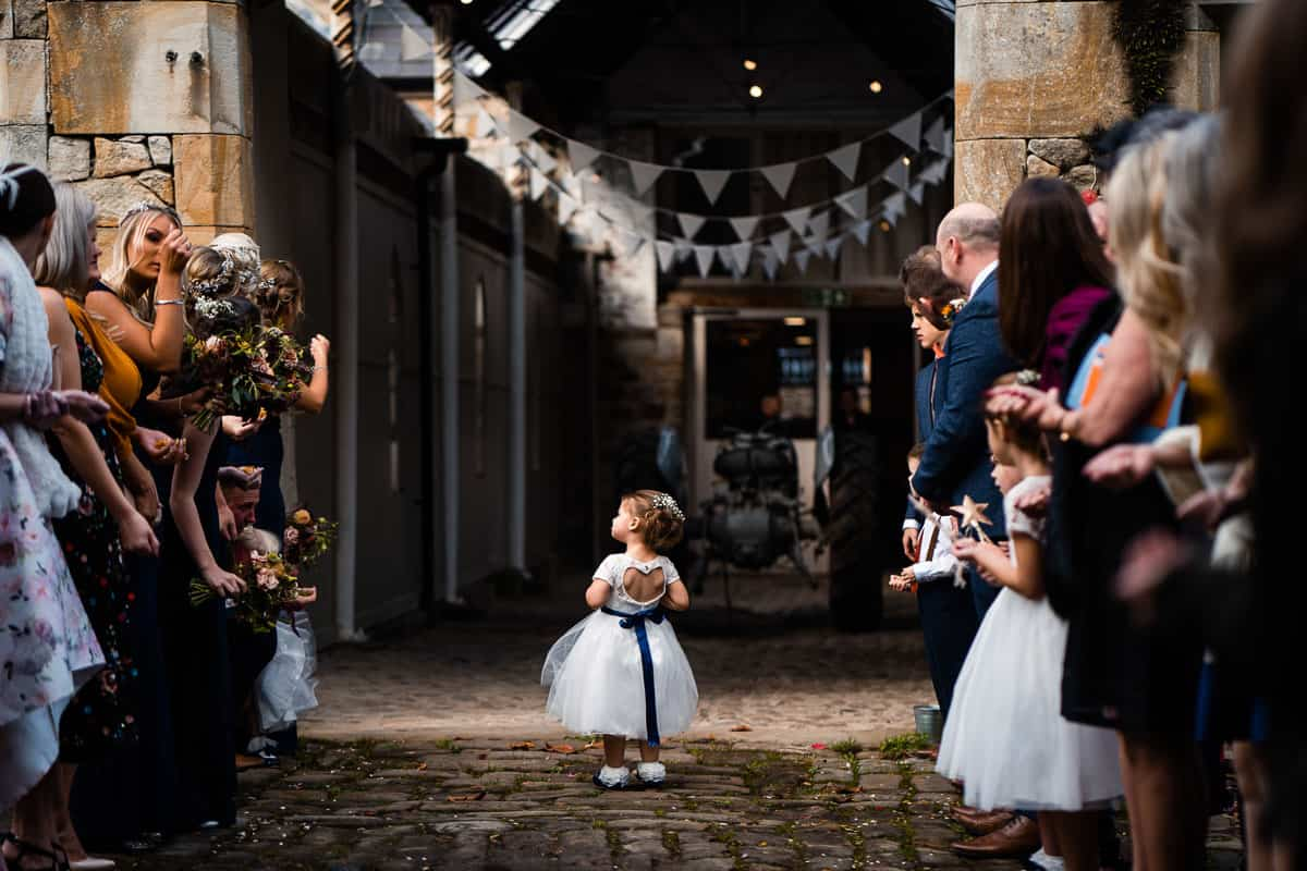 young flower girl in white dress waiting for the couple to come out of the wedding barn
