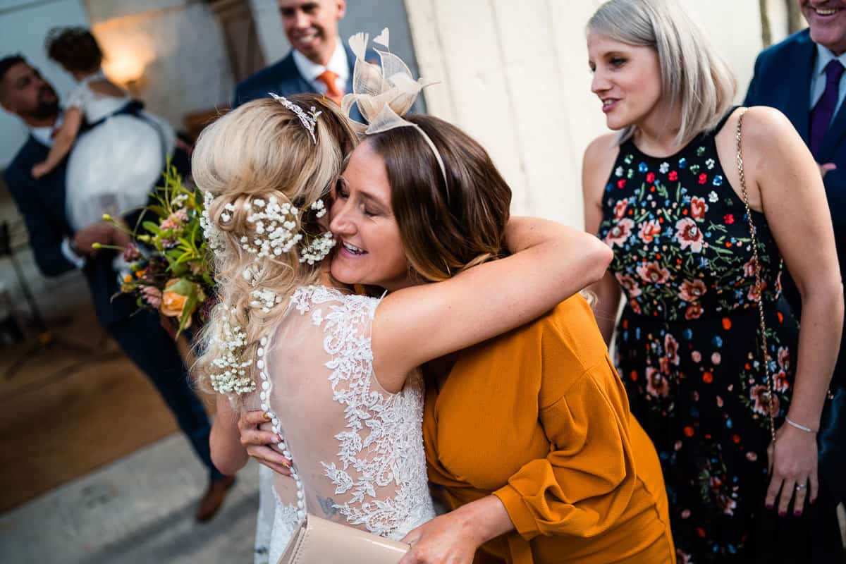 guest in orange dress giving the bride a hug