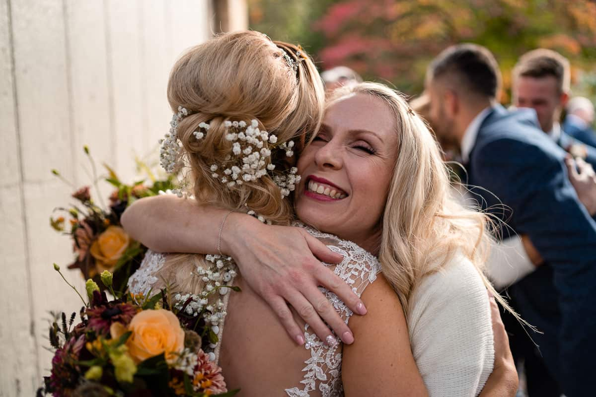 guests smiling and giving bride a hug