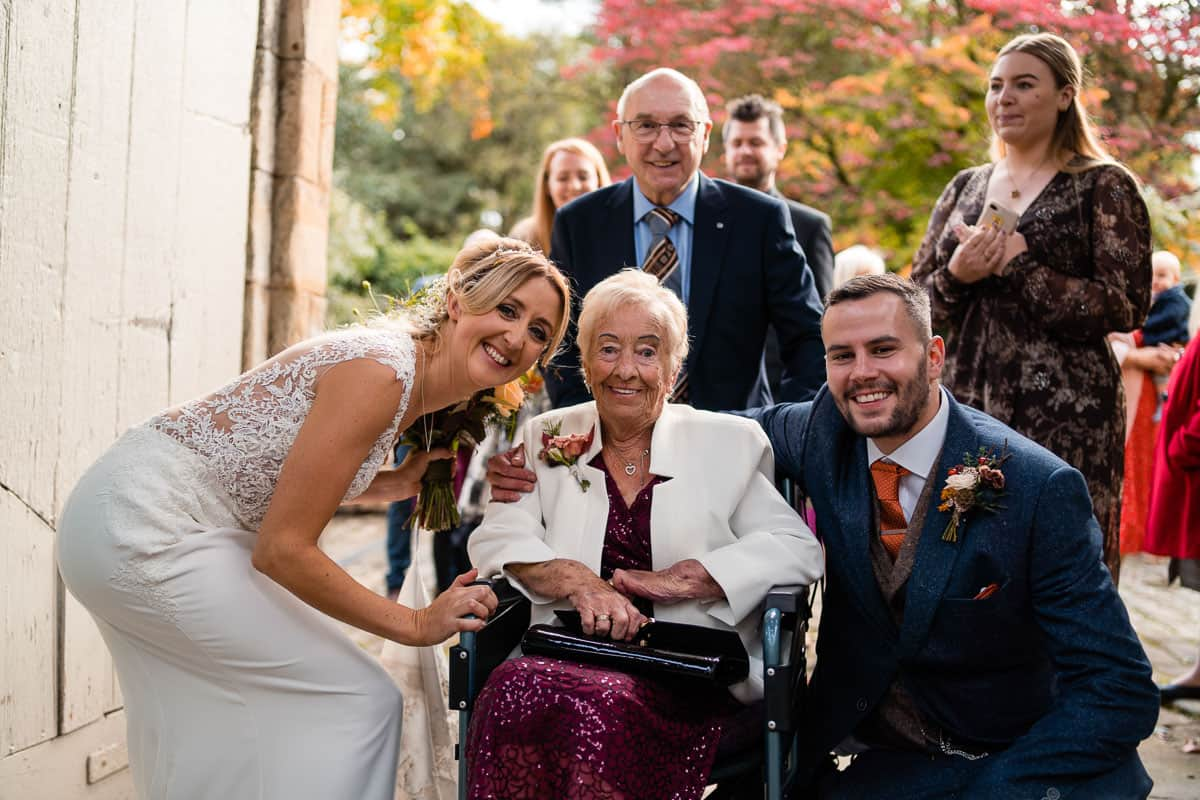 wedding couple posing for photograph with grandparent