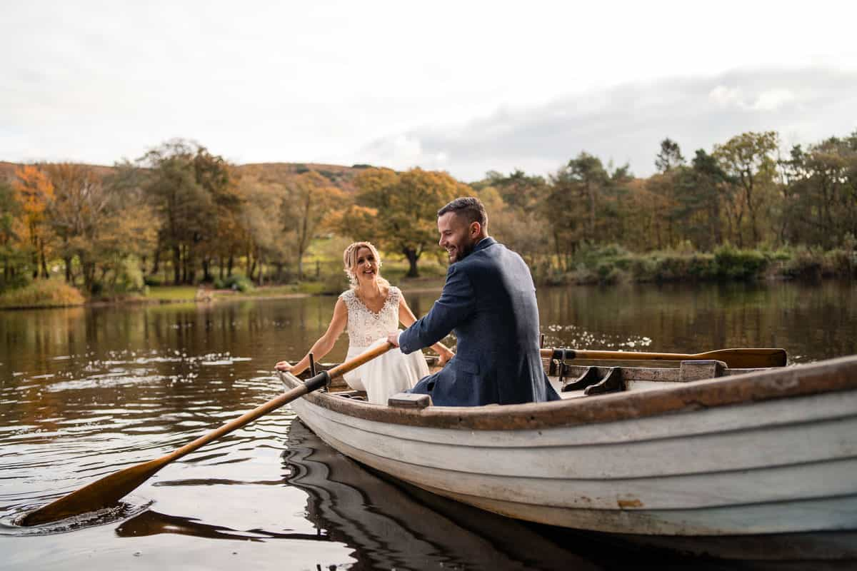 bride and groom in rowing boat smiling at Wyresdale Park