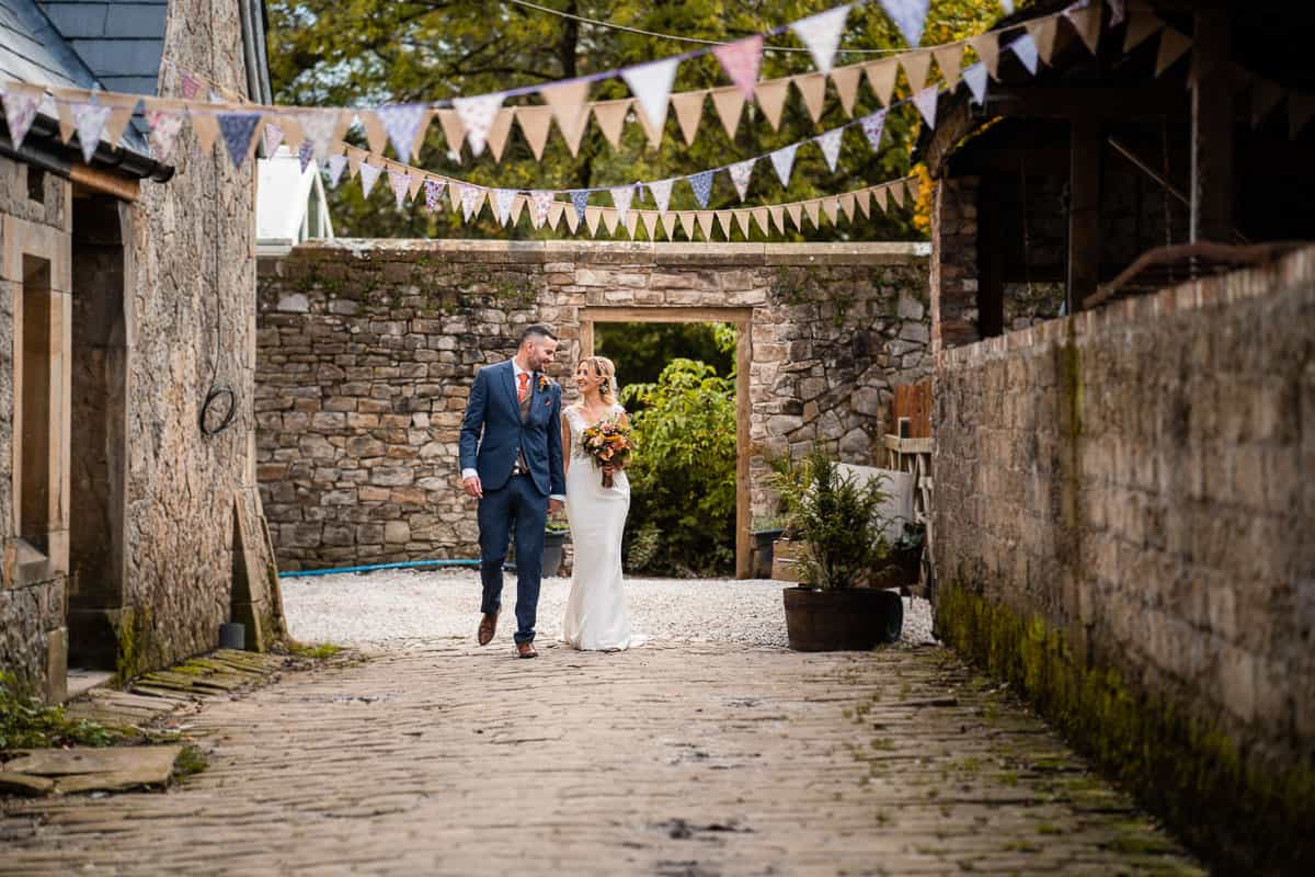 bride and groom walking down cobbled street at Wyresdale Park