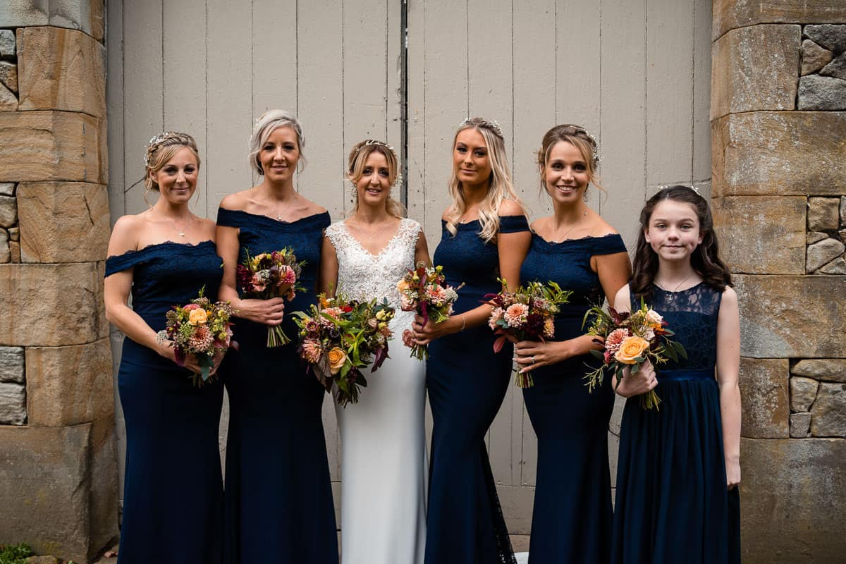 bride with her bridesmaids wearing navy blue dresses