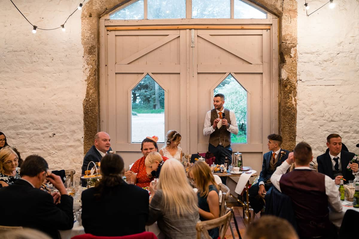 groom stood up to do speech in the barn