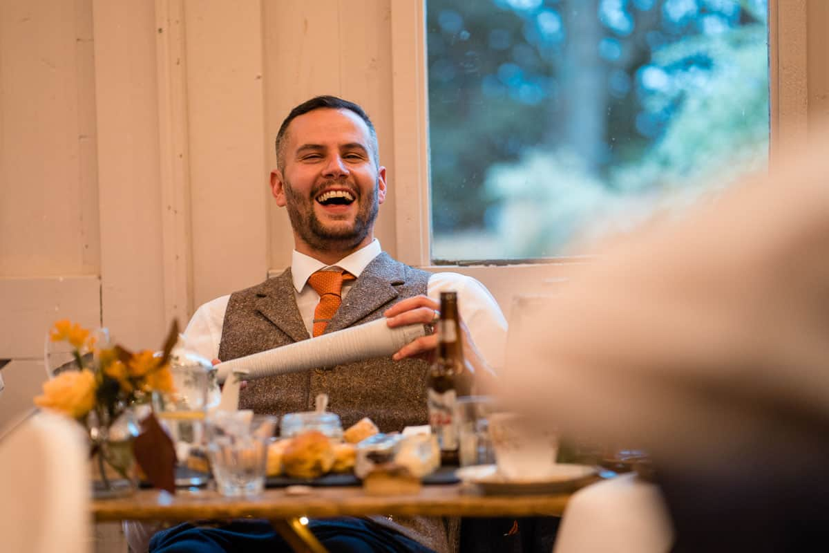 groom sat down laughing whilst best man makes funny speech