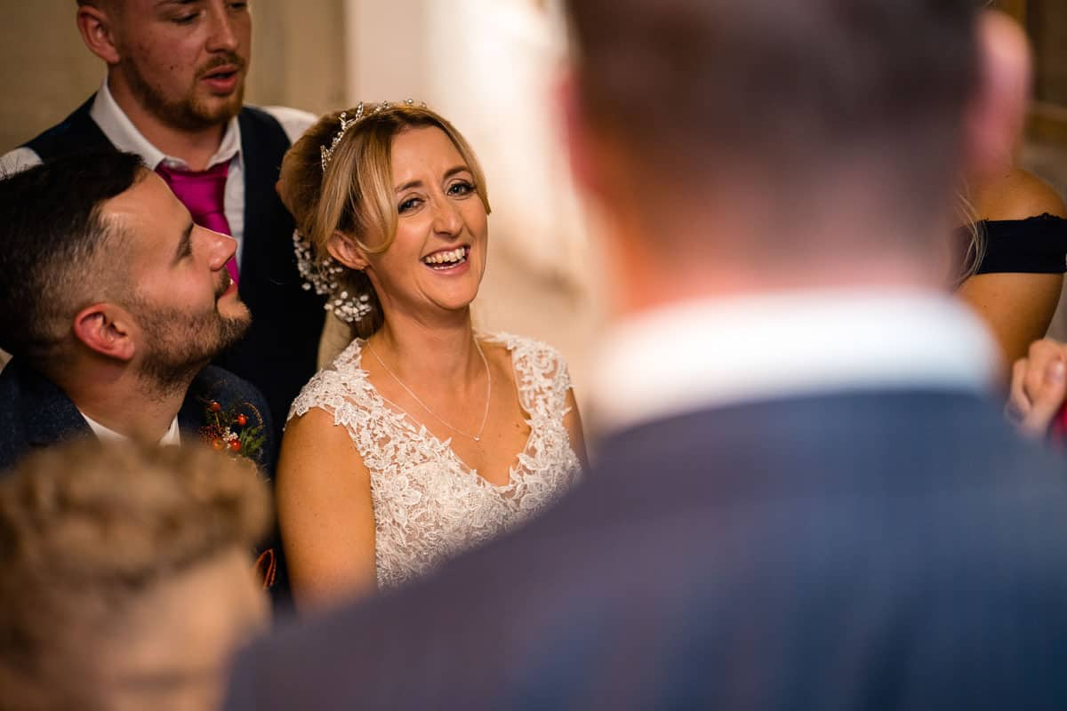 bride laughing as she watches magician