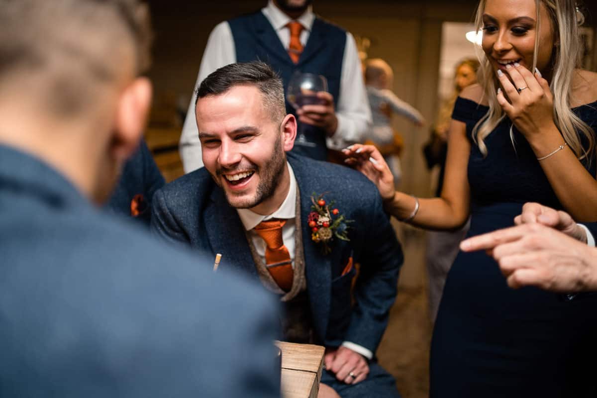 groom smiling as magician does tricks