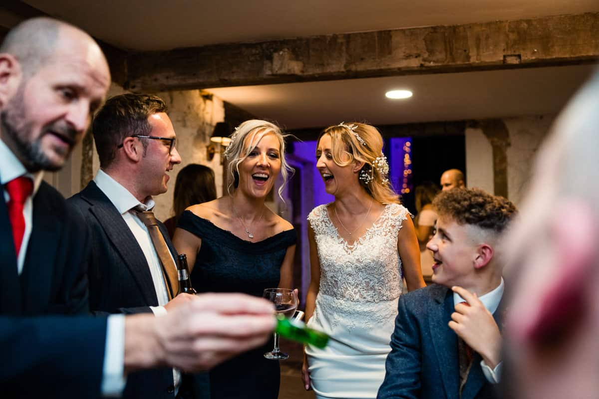 bride and bridesmaid laughing with magician
