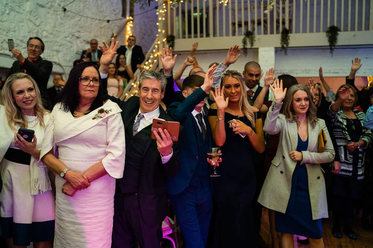 guests with arms up cheering as bride and groom enter