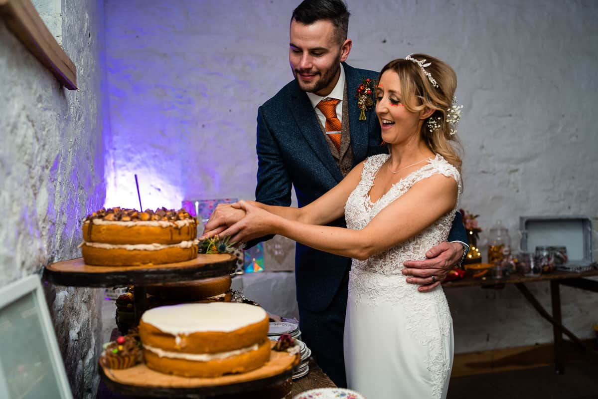 couple are cutting the wedding cake with knife