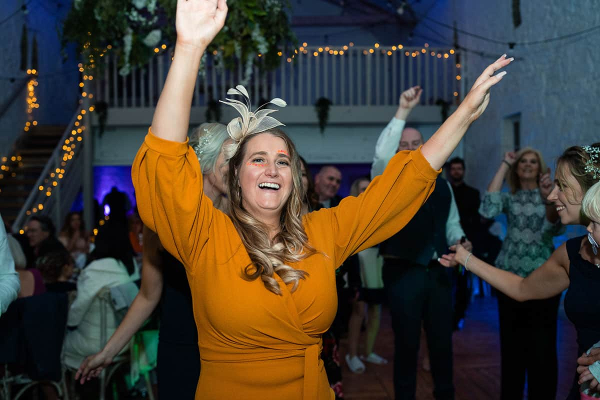 wedding guest with arms up dancing