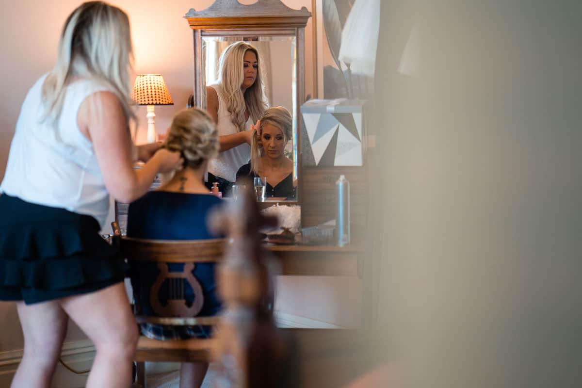 bridesmaid having hair done in mirror