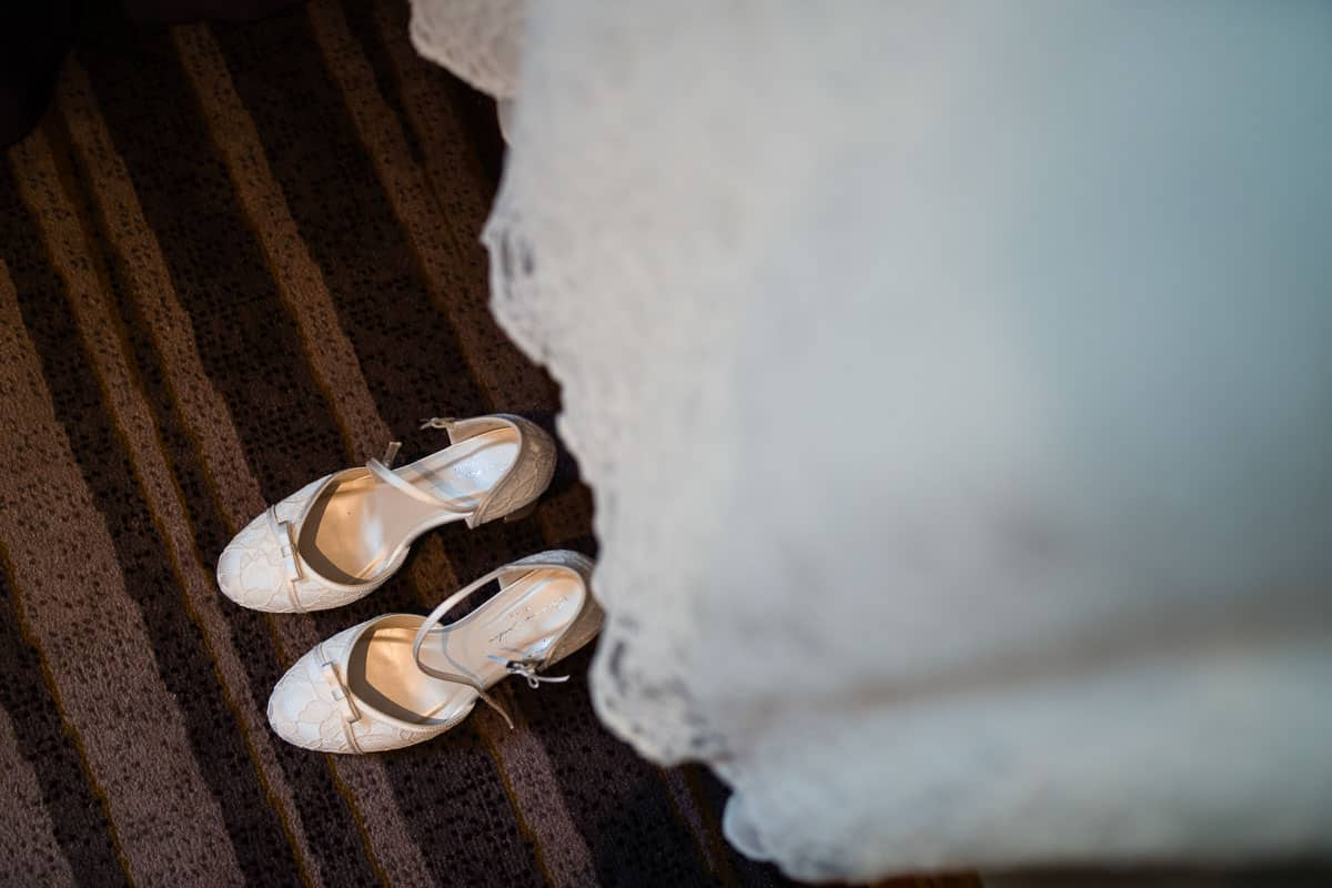 photo of brides shoes sitting under wedding dress