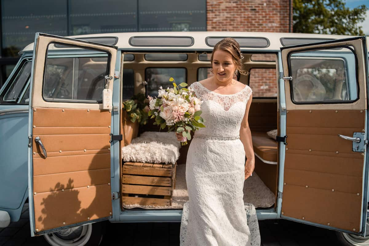 bride stepping out of vintage camper with bouquet