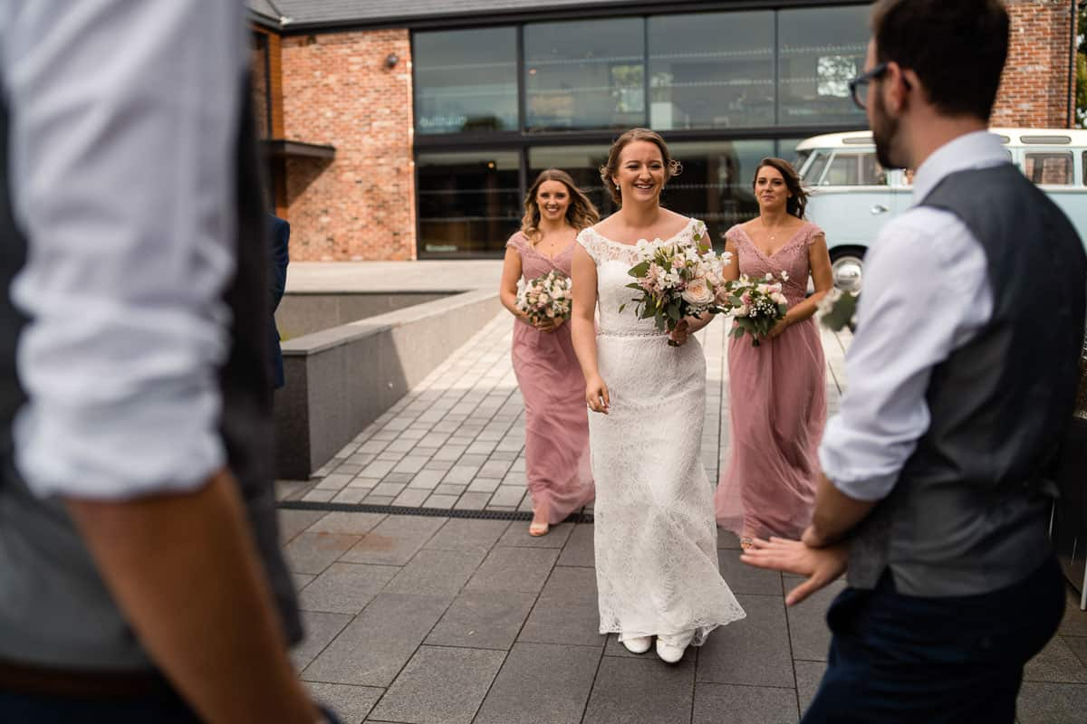 bride walking with bridesmaids outside the colony hq