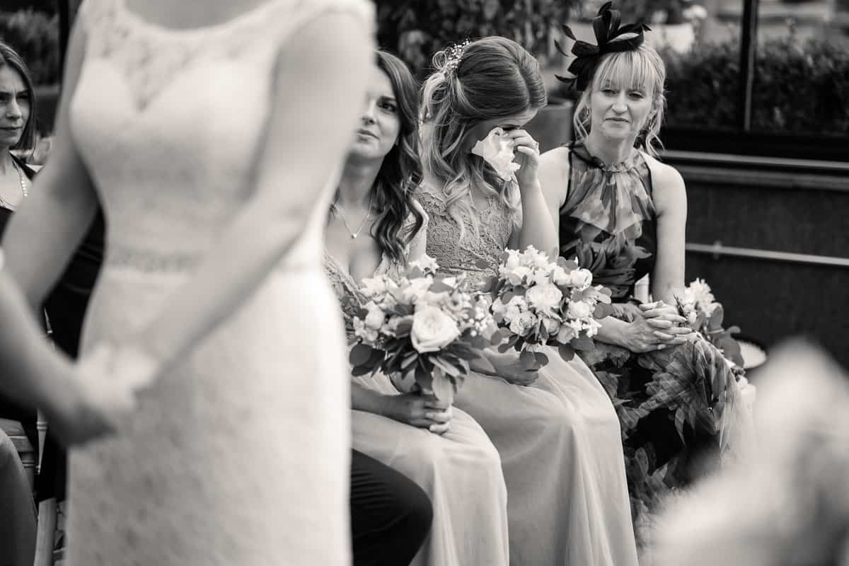 bridesmaid crying and wiping her eye with a tissue during the ceremony
