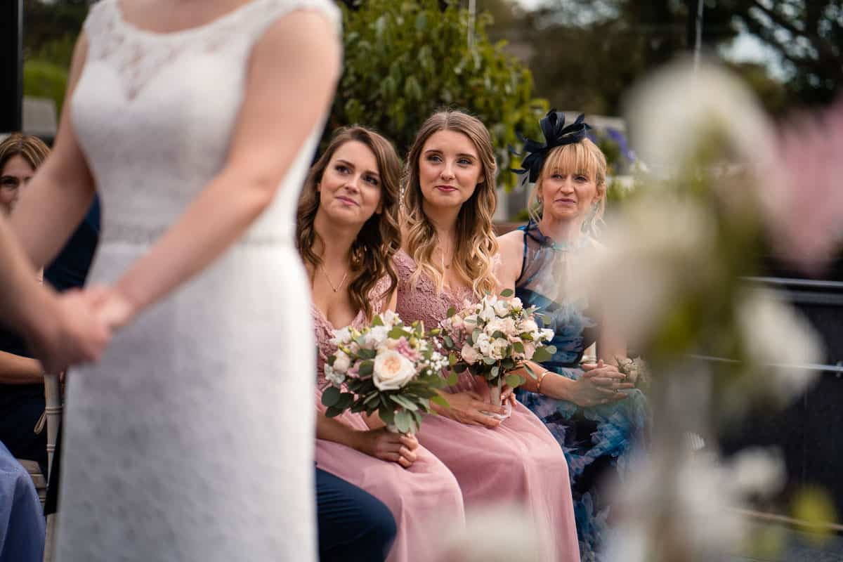 bridesmaids looking at the couple
