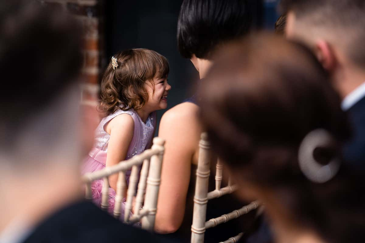 flower girl wearing pink dress smiling at guests on the row behind