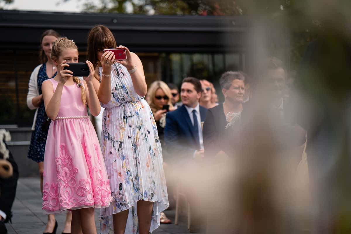 wedding guests taking photographs with mobile phones