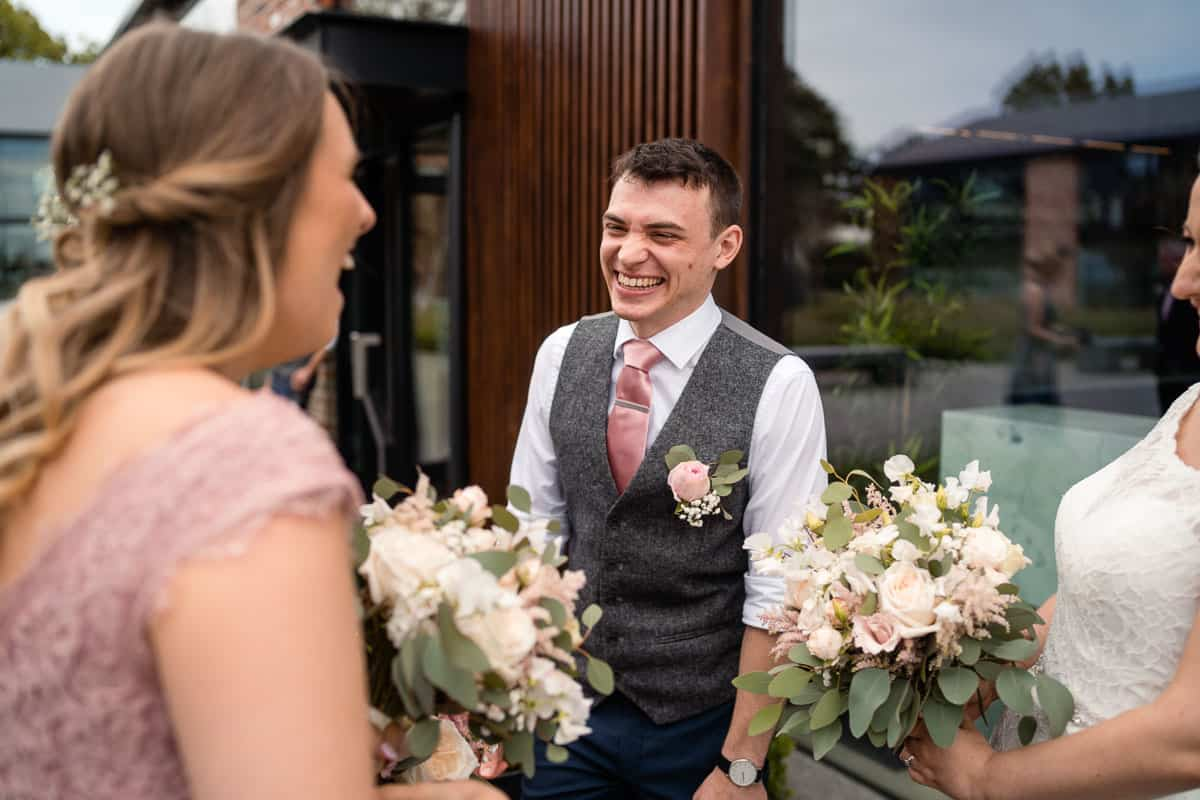 groom laughing with bride and bridesmaid