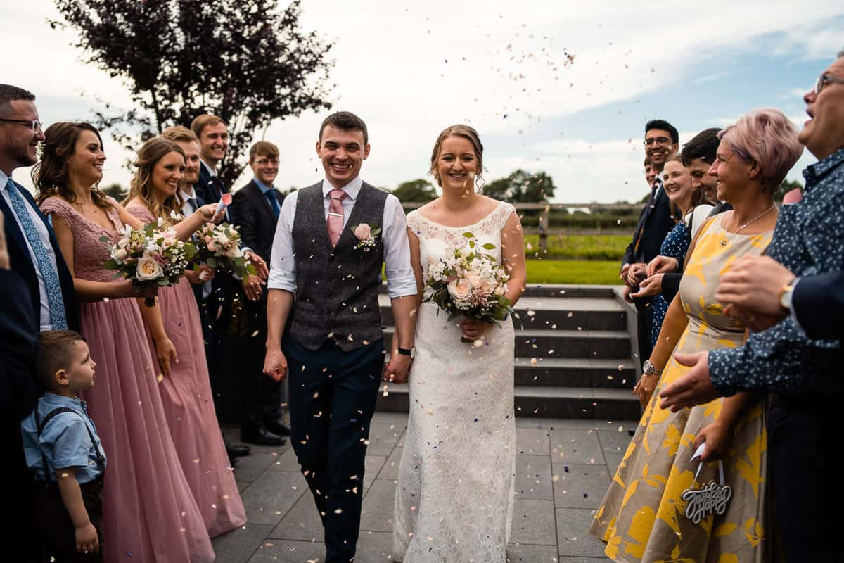 bride and groom with guests throwing confetti outside the colony hq