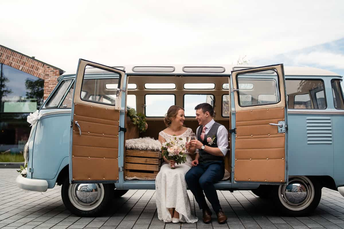 couple sat with the doors open on vintage VW camper van