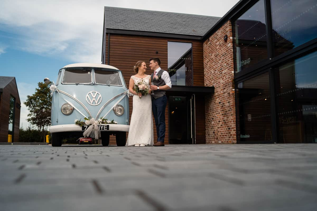 bride and groom outside the colony hq wedding venue with blue vintage camper van