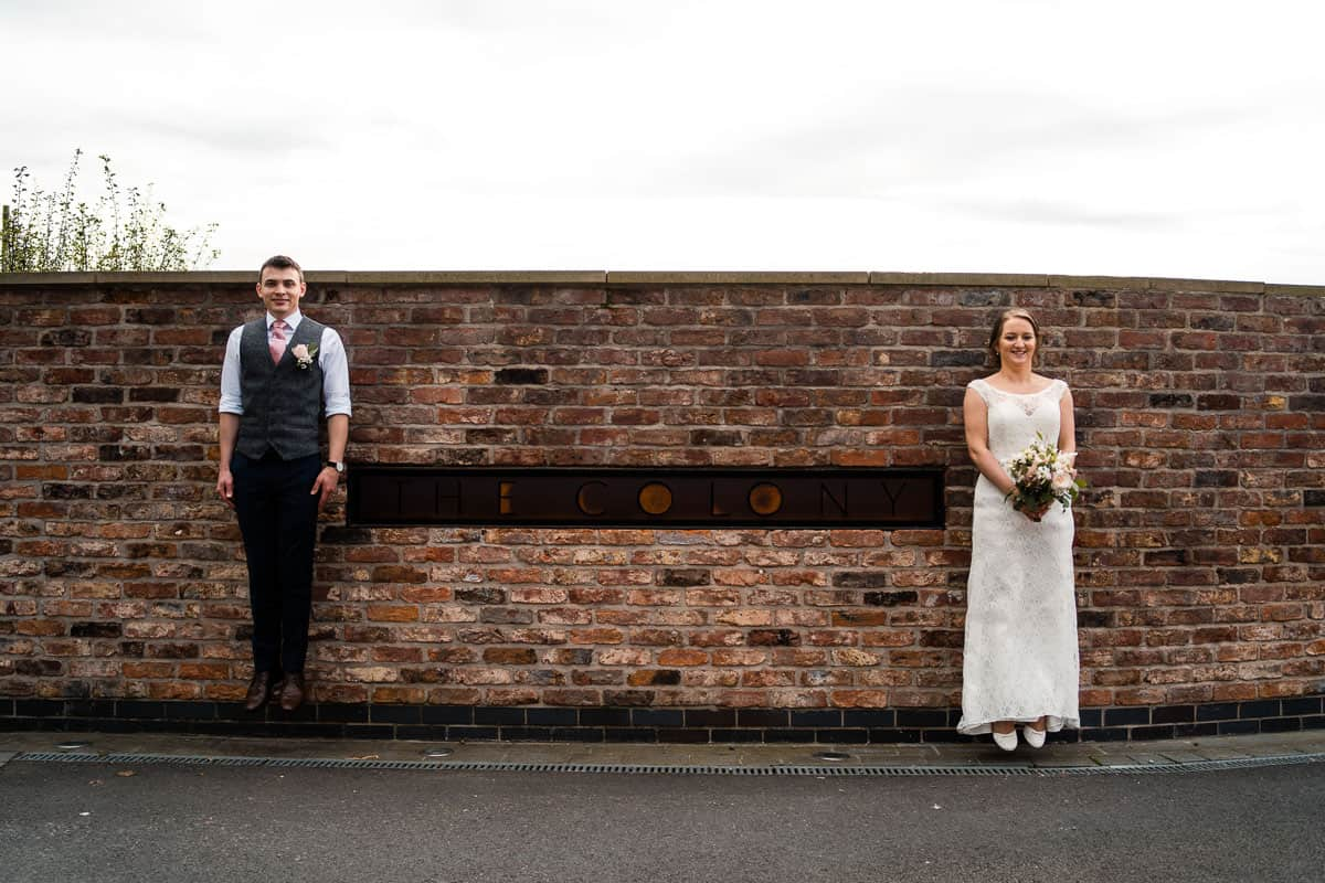 alternative bride and groom portrait with the colony sign