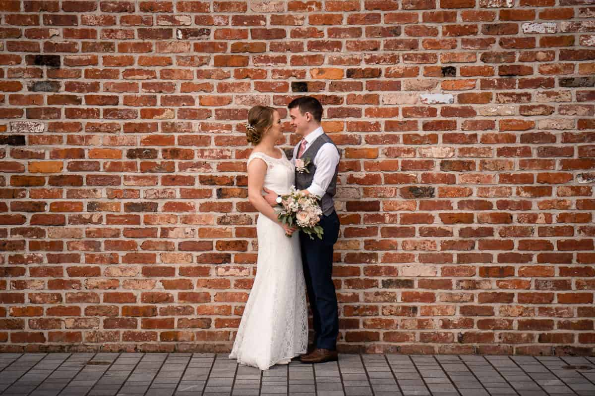 couple portrait in front of brick wall