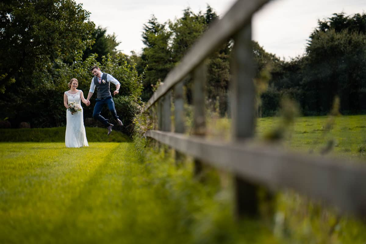 groom jumping holding hand with bride