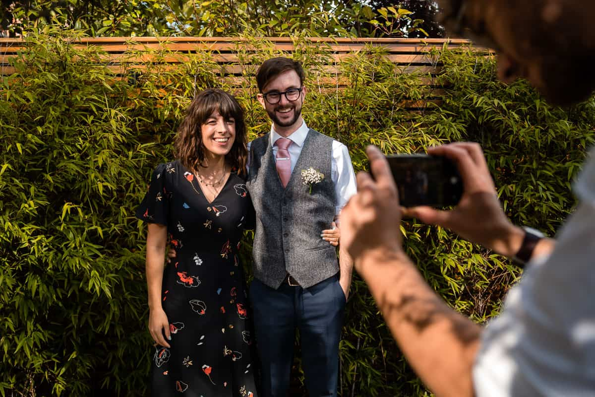 guest taking photographs of couple on mobile