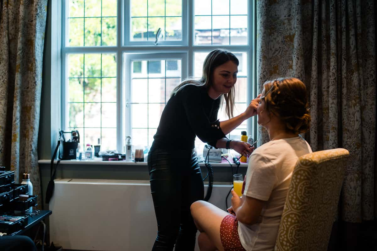 bride having makeup done in front of window
