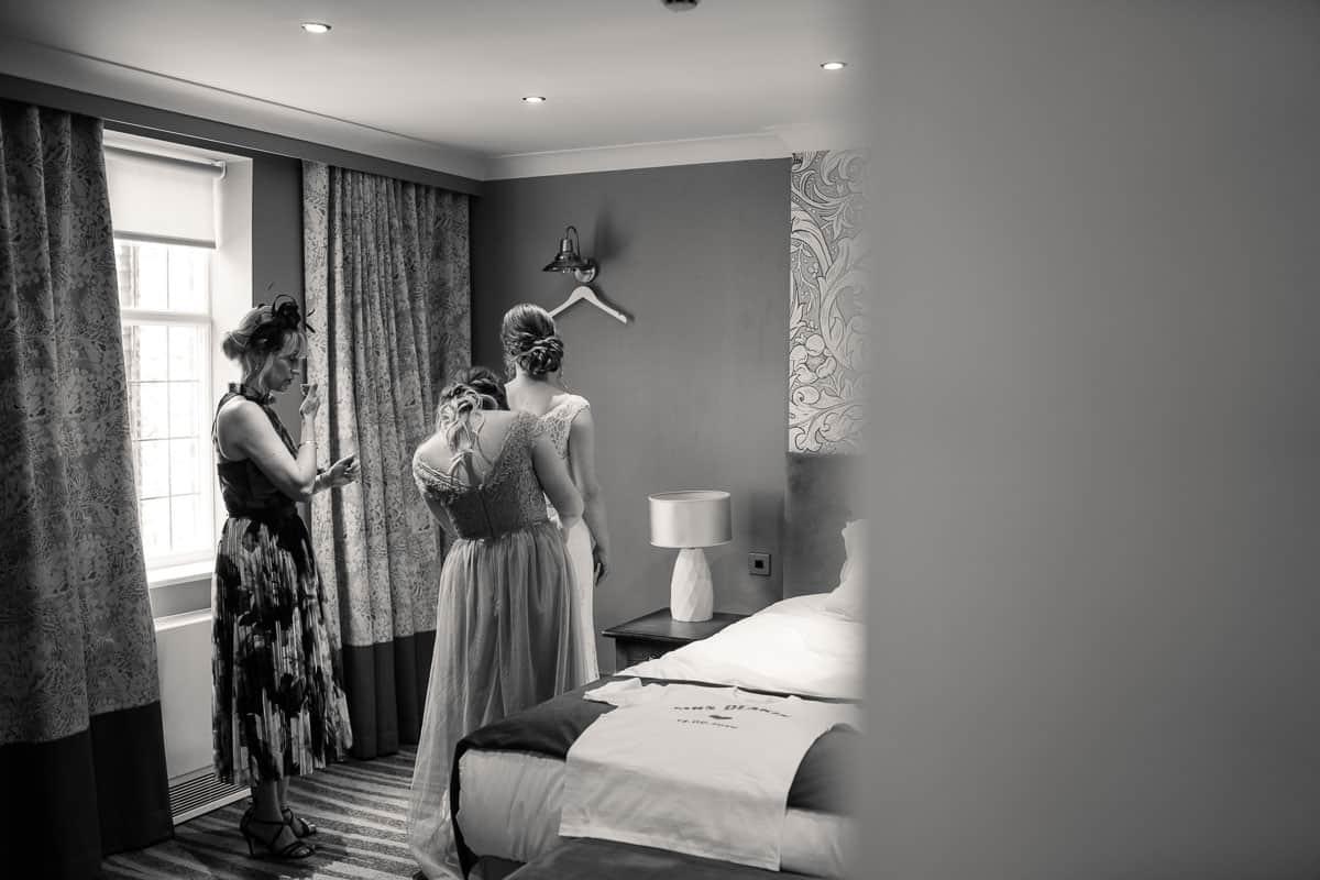bridesmaids helping bride get in her wedding dress
