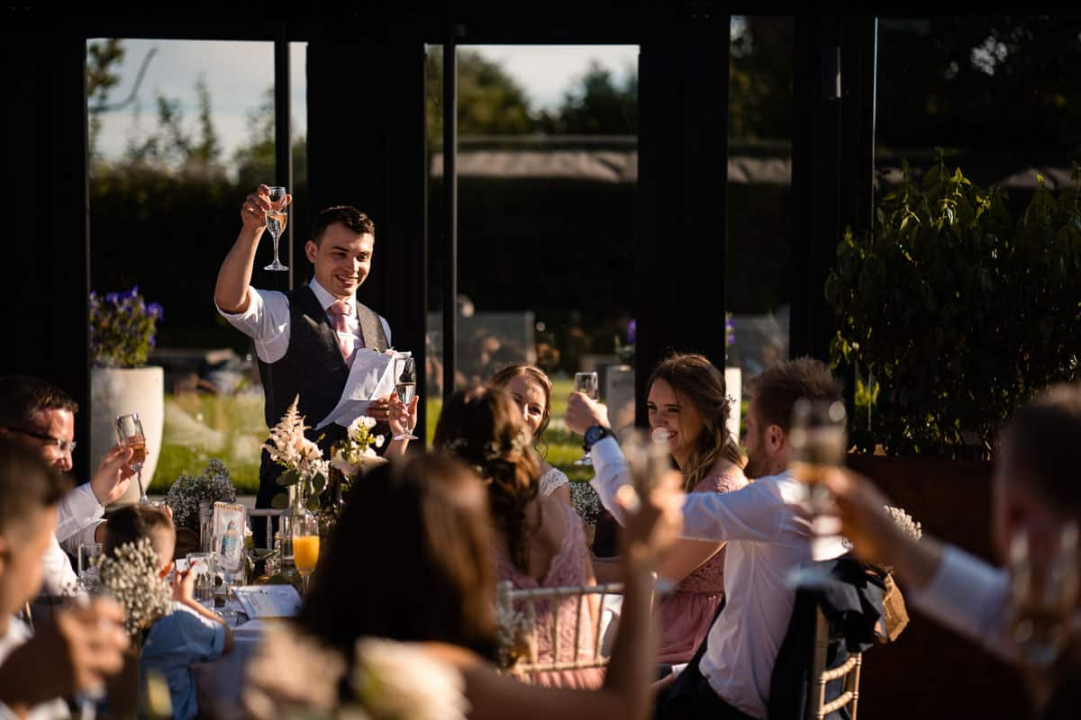 groom raising glass whilst doing speech