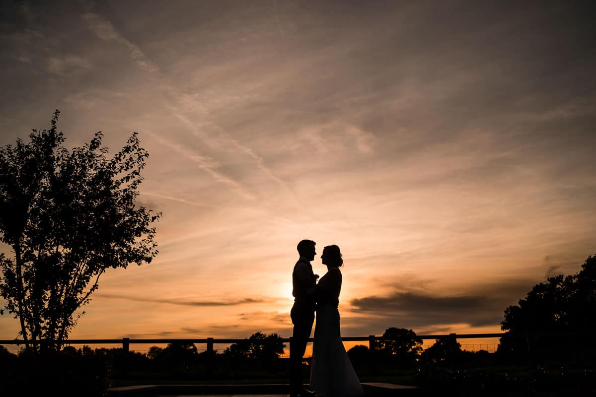 bride and groom portrait with sunset